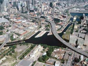 Vue aérienne de l'autoroute Bonaventure et du canal Lachine avec le centre-ville de Montréal en arrière-plan