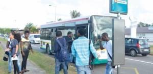 Des lycéens attendant un bus scolaire à un arrêt dans la région de Cayenne